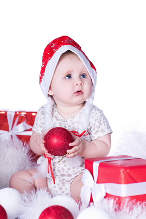 Little cute baby girl, in a red hat of Santa Claus, sits surrounded by red and white Christmas balls, red gift boxes and garlands, isolated over white background. New Year and Christmas holidays. Foto de archivo