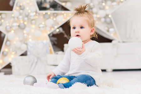 Little cute baby girl sits in a white sweater on a background of Christmas trees, lights, garlands, Christmas balls and gift boxes. New Year and Christmas holidays. Stock Photo
