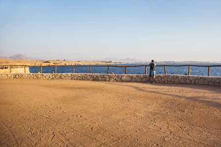 silhouette of a traveling man with backpack stands on the yellow sand near the fence of stone and wood and looks into the distance on the blue sea