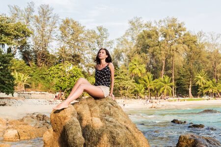 Young beautiful woman on the tropical sea and beach background. brunette girl in summer clothes is sitting on the rock in a summer sunny day 版權商用圖片