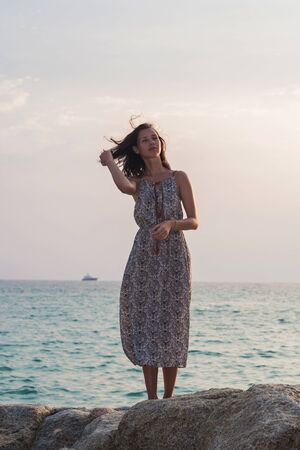 Young beautiful woman over tropical sea and beach background. brunette girl in summer dress stands on the rock in a summer sunny day
