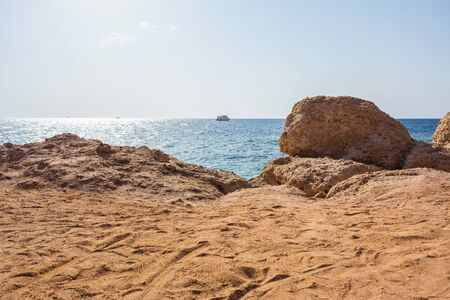 landscape picture background of a beach with sand mounds, stones cliff, blue sea with waves and sky