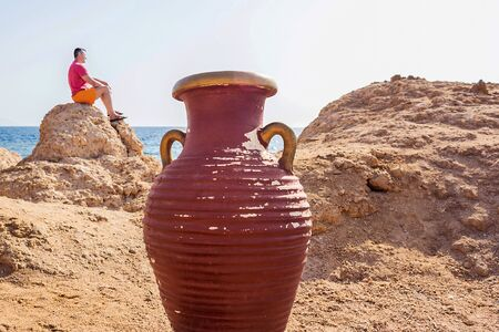 Photo of a large jug against the background of the sea and the beach. A man sits on a stone in the distance