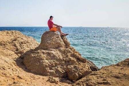a man sits on a stone and looks into the distance on the blue sea. travel and vacation concept
