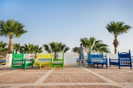 man stands near the multi-colored benches and looks into the distance on the palm trees and blue sky