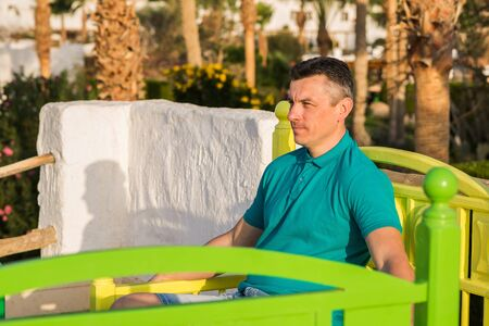 portrait of man over palms trees and blue sky background. guy sits on a bright colored bench and looks into the distance