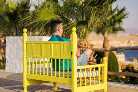 man traveler sits on a bright colored bench and looks into the distance, on a palms trees and blue sky background