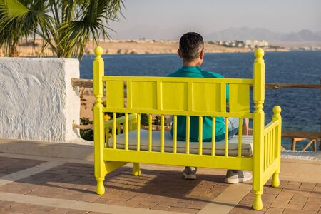 man traveler sits on a bright colored bench and looks into the distance, on a palms trees and blue sky background 免版税图像 - 126679576