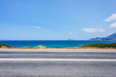 ?ar travel concept on Crete island, Greece. landscape of blue sea, sky, mountains, against the background of the road Standard-Bild
