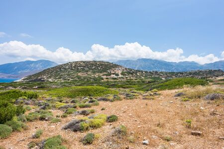 Natural landscape of hills, sand, grass, sea, clouds and blue sky on the island of Crete, Greece