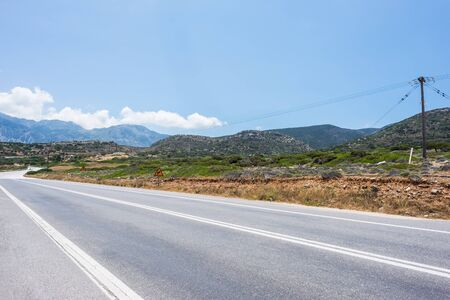 ?ar travel concept on Crete island, Greece. landscape of blue sea, sky, mountains, grass and sand against the background of the road stretching into the distance