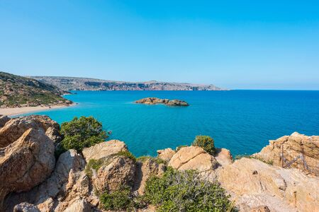 Natural landscape of mountains, hills, sand, grass, sea, clouds and blue sky on the Crete Island Greece, Vai beach 免版税图像 - 126679753