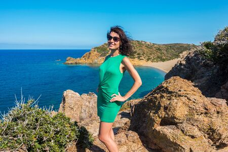 Beautiful girl in green dress is enjoying the crystal clear sea and sunny day from view point on Vai bay, Crete, Greece 免版税图像