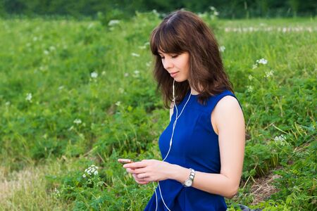 girl sits in the park on the grass and listens to music through headphones by phone 免版税图像