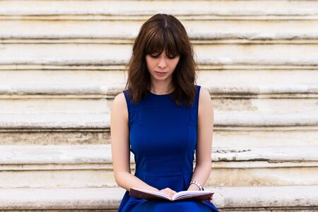 beautiful young girl in blue dress sitting on the steps and reading a book