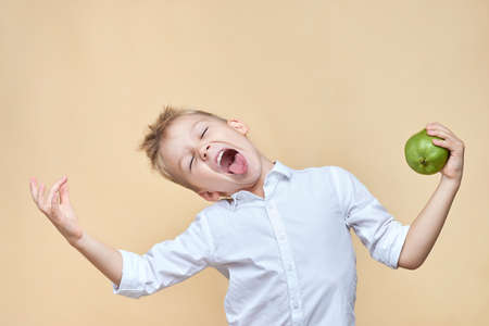 ? ute disheveled boy indulges and grimaces holding a pear in his hands.