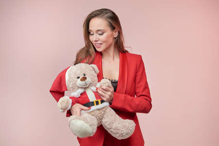 Smiling beautyful woman in a red jacket lovingly looks at a toy bear in the image of Santa Claus. New Year concept.