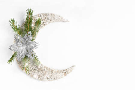 Snowy fir tree branch and silver flower or star on white crescent. Top view with copy space. Flat lay. Christmas background or postcard. New year concept.
