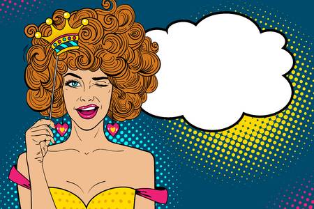 Pop art face. Young sexy ginger woman holding funny paper crown on stick, smiling and winking and empty speech bubble. Vector illustration in retro comic style. Holiday party invitation poster.  イラスト・ベクター素材