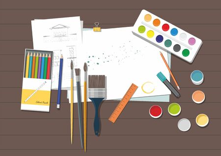 Brushes, paints, colored pencils and paper on the wooden background.