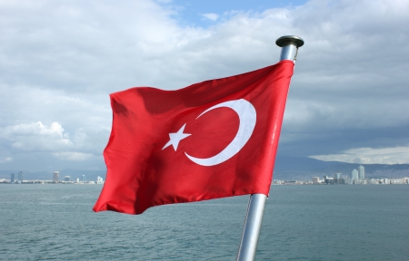 Turkey flag with metal shaft on Izmir bay background