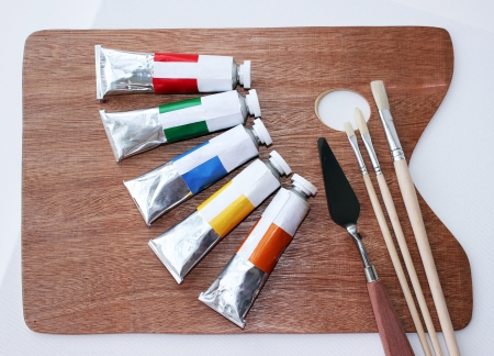 New oil paints in tubes on palette with brushes and palette knife and canvas photo