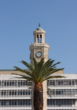 Fragment of Ancient clock tower  Saat Kulesi  with palm on front at Konak square in Izmir, Turkey photo