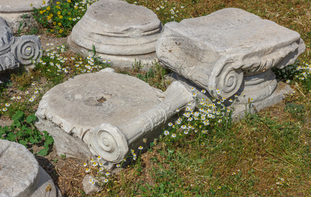 order chaos: Capitals and architectural parts with daisies in the spring in Ancient Agora,  Smirna (Izmir) Turkey. Agora under restoration Stock Photo