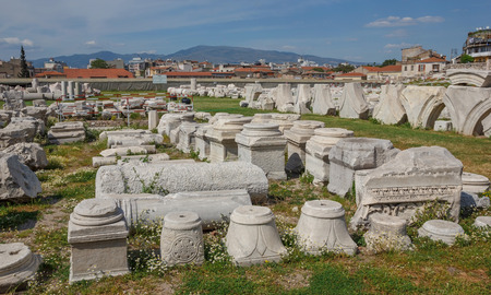 past civilizations: Capitals and architectural parts with daisies in the spring in Ancient Agora,  Smirna (Izmir) Turkey. Agora under restoration Stock Photo