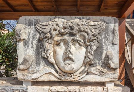 friso: Parte de arquitrabe con friso con el gigante mítico cabeza gorgona Medusa en el antiguo templo de Apolo en Didim, Turquía