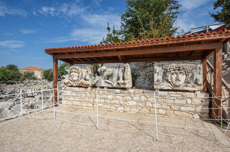 frieze: exposure with parts of architrave with a frieze with mythical giant Gorgons Medusas heads in ancient Temple of Apollo in Didim, Turkey Stock Photo