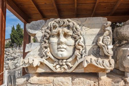 friso: Arquitrabe de la parte con friso con mítico gigante cabeza gorgona Medusa en el antiguo templo de Apolo en Didim, Turquía Foto de archivo