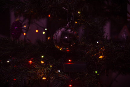 bl: Christmas background with tree toy in blur effect and bokeh. Photo toned purple dark