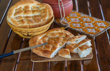 breadbasket: Ramadan pide cut and outdoor served with rasary, breadbasket  and pottery. photo with shallow depth of field Stock Photo