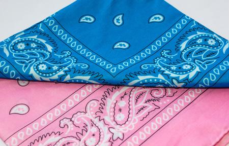 Folded blue and pink bandanna on white background