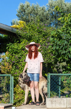 kangal: young girl in a hat with a Turkish Kangal Dog on natural summer garden background