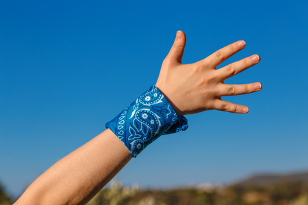 female hand with a blue bandana with palm hand on nature background (bunch of fives) 版權商用圖片