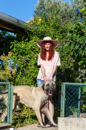 young girl in a hat with a Turkish Kangal Dog on natural summer garden background