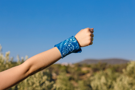 hand with fist  and blue with knotted bandana on nature background Stock Photo