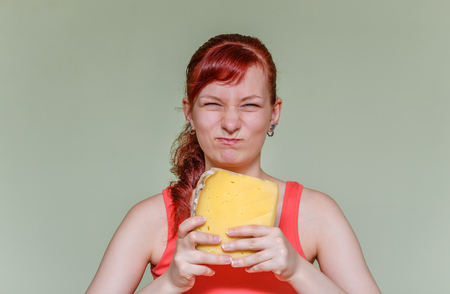 grimace: young girl with a sour grimace with a piece of cheddar cheese Stock Photo