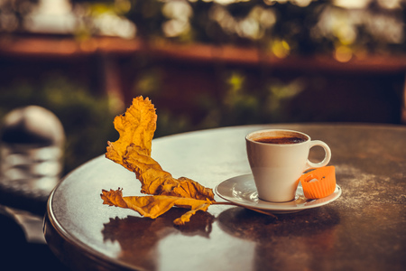 frothy: Turkish coffee in a white cup with candy in paper and dry yellow autumn leave on the table. Photo toned with shallow depth of field Stock Photo
