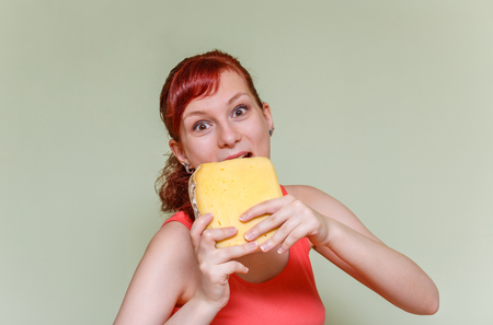 expressive face: young beautiful girl bites cheddar cheese on green background Stock Photo
