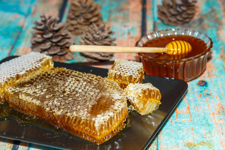 Famous Marmaris (Turkey) pine honey comb and liquid honey on surface imitating wood  with cones. Photo toned Reklamní fotografie
