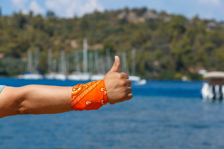 mans hand with raised thumb with orange bandana against the backdrop of marina Marmaris