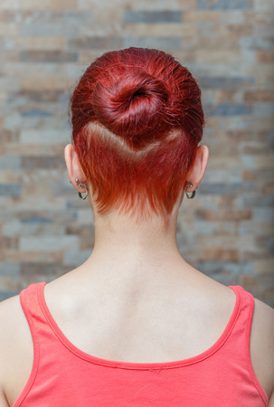 topknot: young model with topknot and hidden undercut on hair