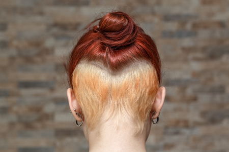 topknot: young model with colored topknot and hidden undercut bleached hair Stock Photo