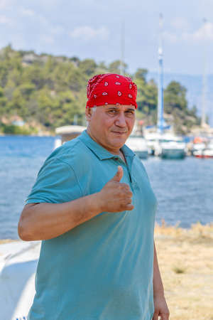 super yacht: man in red bandana with raised thumb against the backdrop of marina Marmaris