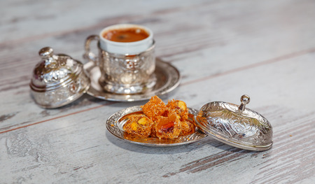Turkish delight with kadaif and pistachios and Turkish coffee in beautiful metal bowl with  oriental pattern on the wooden table. Photo with shallow depth of field