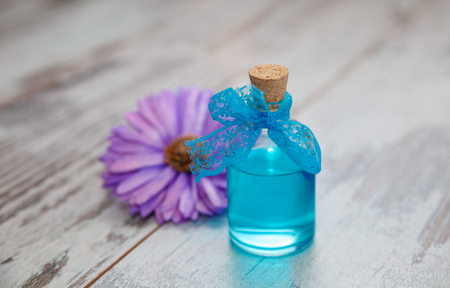 blue cologne in small bottle and dry flower on old tree background.  Photo with shallow depth of field