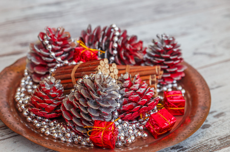 christmas decorations of colored cones sticks beads on a copper tray on a light gray - Copper Christmas Decorations